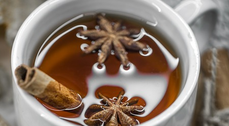 punch spice: a Cup of hot tea with cinnamon sticks and spices on wooden background