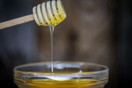 wooden spoon for honey,dripping a drop of honey closeup