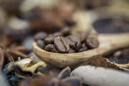 cafe colombiano: fragrant coffee beans in a beautiful wooden spoon on wooden background