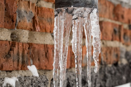 water frozen: Natural icicles hanging on the pipe, the concept of winter
