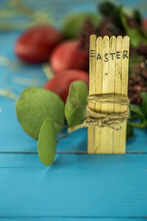 the word Easter in the conceptual block text on wooden sticks, beautiful festive eggs with greens Stock Photo