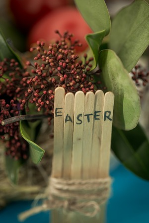 greens: the word Easter in the conceptual block text on wooden sticks, beautiful festive eggs with greens Stock Photo