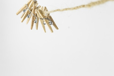 pretty little decorative clothespins weigh on the rope, isolated on white background