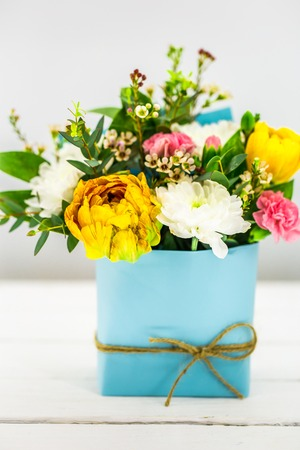 live spring flowers on a white background in a blue pot with bow