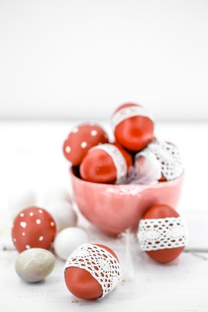 Red Easter eggs on white background tied lace tape , close-up , lie on wooden background, still life Stock Photo