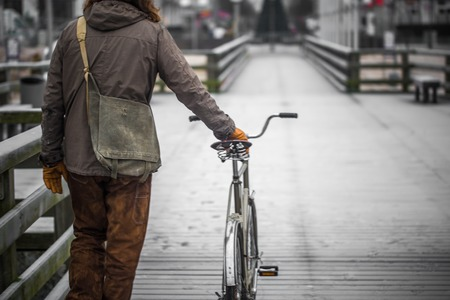 vestidos antiguos: a single man dressed in old clothes on the embankment with the bike Foto de archivo