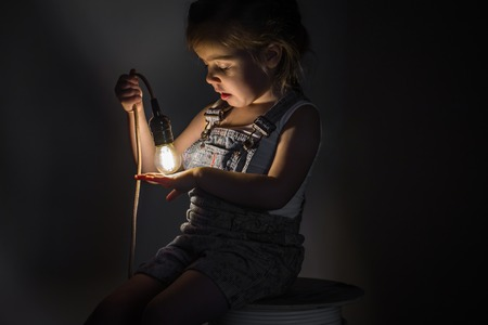 klein schattig meisje met een lamp in de hand zitten op de Streng van draden voor elektriciens, concept ideeën