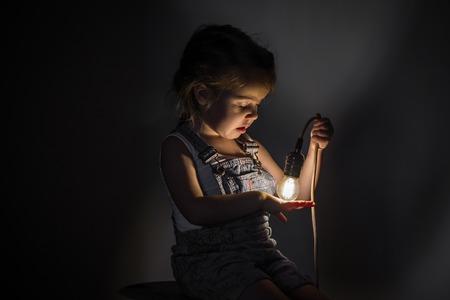 klein schattig meisje met een lamp in de hand zitten op de Streng van draden voor elektriciens, concept ideeën Stockfoto