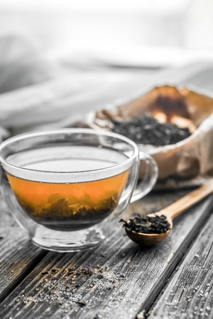 transparent Cup of tea brewed with adjacent wooden spoons, sugar and tea on wooden background