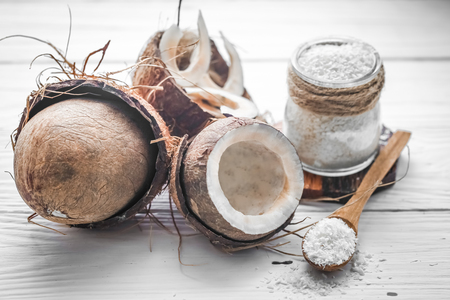 filings: Still life with coconut and coconut flakes in wooden spoons and glass jar on wooden background