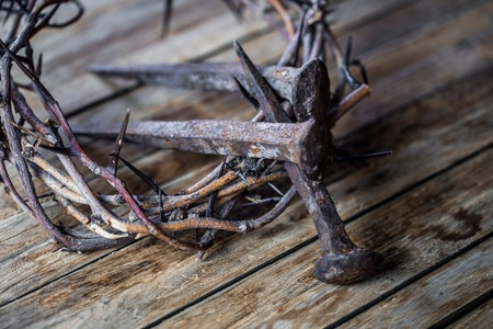 The crown of thorns and the nails on wooden background Easter concept