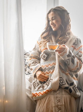 Cozy transparent Cup of tea at a cute girl in a warm knitted sweater against the window