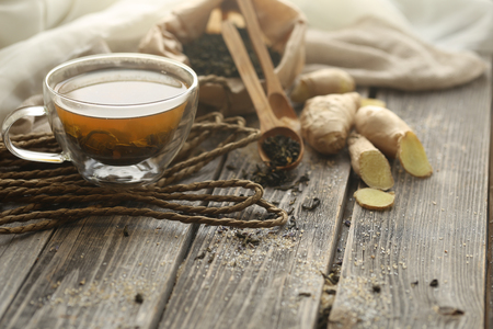 still life with transparent and fragrant Cup of tea with ginger on wooden background