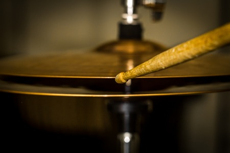 plays a drum stick on the hi-hat or ride cymbal, drums, percussion musical instrument, photo closeup