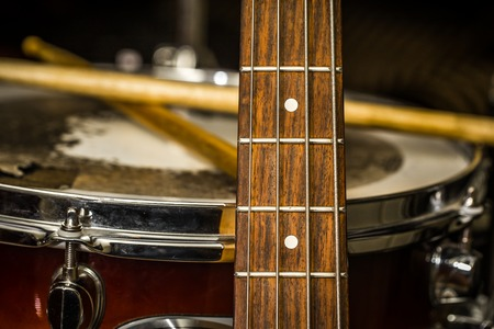 drum and bass: snare drum with drumsticks and bass guitar, closeup, concept musical composition and creativity