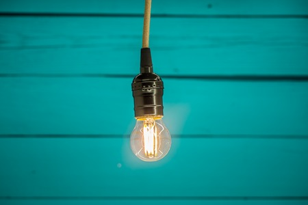 light bulb on blue wooden background, copy space, closeup