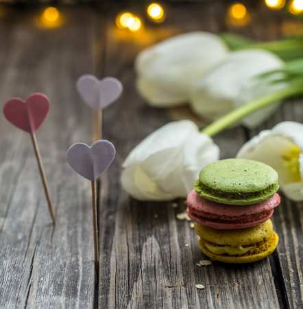 beautiful white tulips and colorful macaroons on wooden background, holiday concept Stock Photo