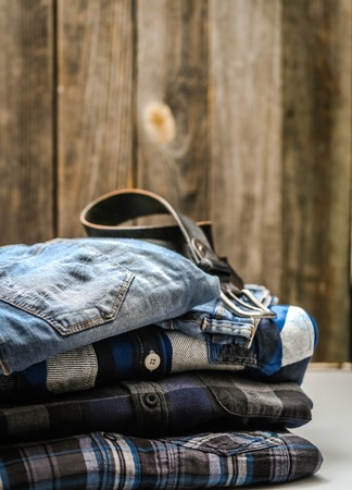 folded mens shirt in the box and the belt with jeans on wooden background ,concept of style and fashion