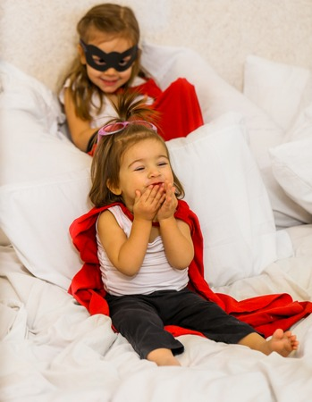 two little girls play costumes super-hero sitting on a white bed,the concept of leadership,victory