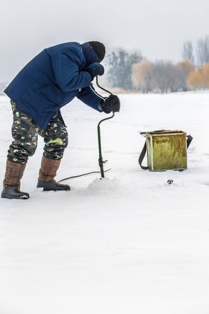 A fisherman on the ice with equipment for winter fishing Stock Photo