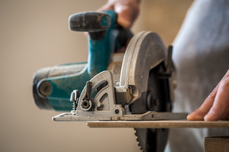 a man cuts a Board manual electric saw ,close-up , concept building and repair Stock Photo