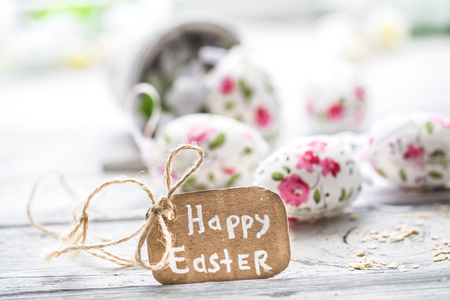 Easter composition with eggs in a bucket and with the inscription happy Easter is on a light wooden background