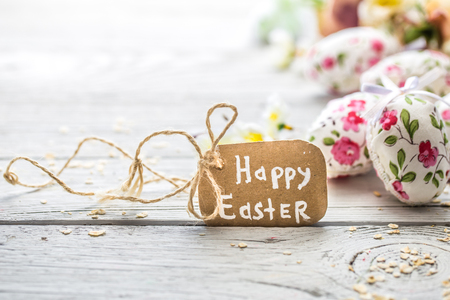 Easter composition with eggs and the words happy Easter is on a light wooden background