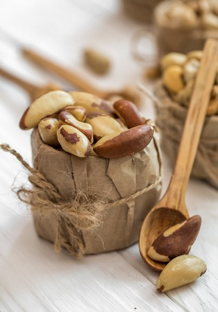albero nocciolo: Brazilian nut and wooden spoons on white wood background closeup ,concept of healthy nutrition