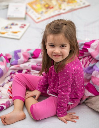 little girl lying on the bed with bare feet ,beautiful smiles,the concept of sleep and rest Imagens