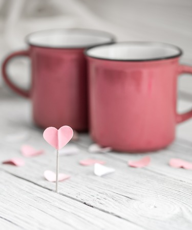 teaparty: beautiful pink Cup with heart on a stick on a light wooden background, concept drinks