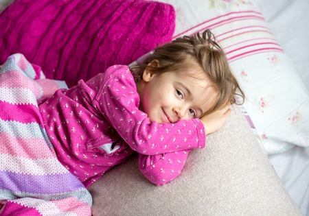 little cute girl sleeping in the pink bed,the concept of childhood and holiday