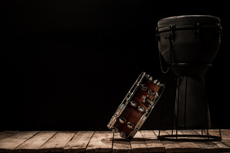 musical percussion instruments on black background drum Bongo and snare ,stands on the wooden floor ,the concept of musical instruments Stock Photo