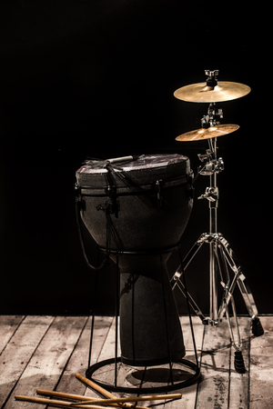 musical percussion instruments on black background drum Bongo and stand with cymbals ,stands on the wooden floor ,the concept of musical instruments
