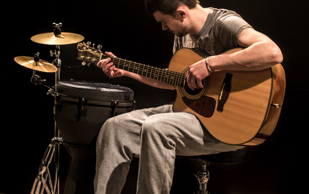 musician plays acoustic guitar and percussion instruments, black background, musical instruments with a young man musician, creative music concept Stock Photo