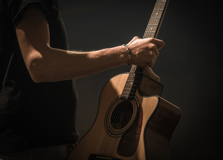 hand jamming: young man with acoustic guitar on black background, creative musical concept