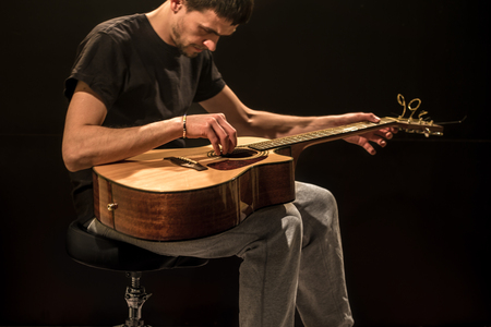 hand jamming: young man with acoustic guitar on black background