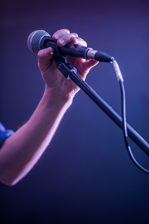 hand with microphone on a black background, the music concept, beautiful lighting on the stage, closeup