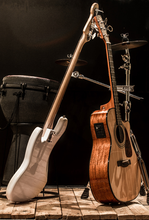 musical instruments, acoustic guitar and bass guitar and percussion instruments drums on a black background, the music concept Stock Photo