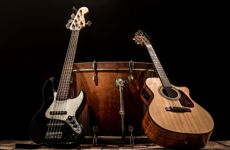 musical instruments, bass drum barrel acoustic guitar and bass guitar on a black background, the music concept Foto de archivo