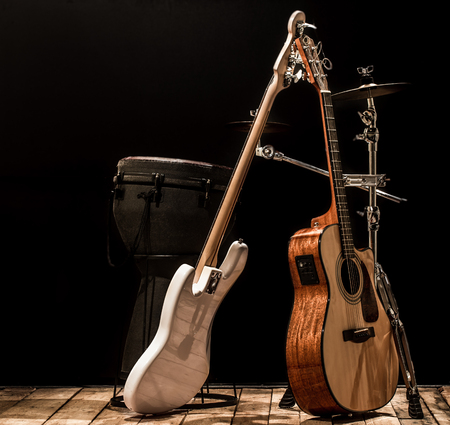 musical instruments, acoustic guitar and bass guitar and percussion instruments drums on a black background, the music concept Banque d'images