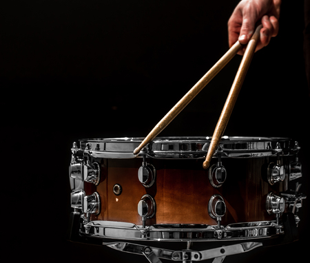 man plays musical percussion instrument with sticks closeup on a black background, a musical concept with the working drum