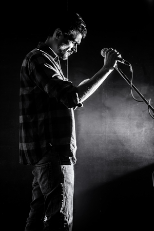man with microphone on a black background, the music concept, beautiful lighting on the stage, closeup