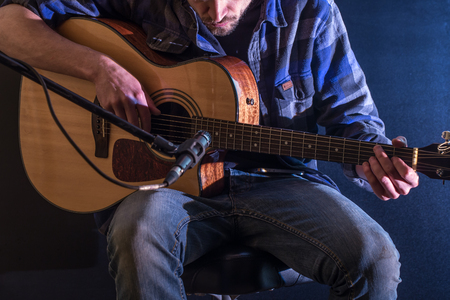 hand jamming: man playing acoustic guitar on a black background, the music concept, beautiful lighting on the stage, closeup