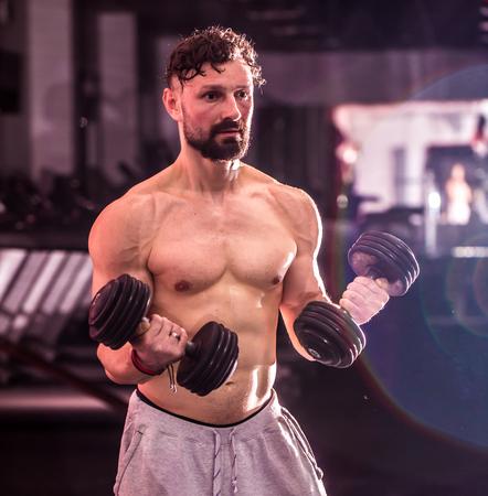 Muskel-Sport-Mann ist in der Ausbildung Kreuz fit in der Turnhalle, das Konzept des Sports engagiert Standard-Bild
