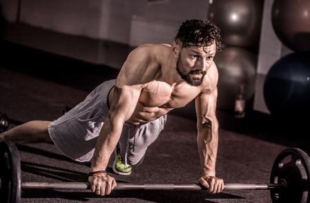 Muscular athletic man has trained cross Fit,do push-UPS in the gym ,sports concept Stock Photo