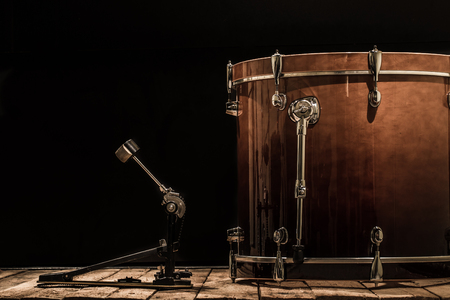 percussion instrument, bass drum with pedal on wooden boards with a black background, the music concept Stock Photo