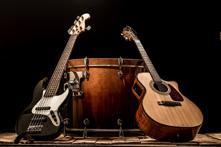 musical instruments, bass drum barrel acoustic guitar and bass guitar on a black background, the music concept Stock Photo