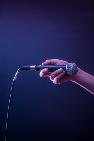 lighting background: hand with microphone on a black background, the music concept, beautiful lighting on the stage, closeup