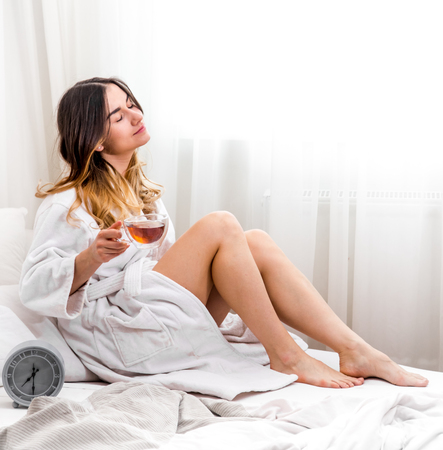 sweetheart satisfied the girl morning in bed with clock , time concept and a good nights sleep