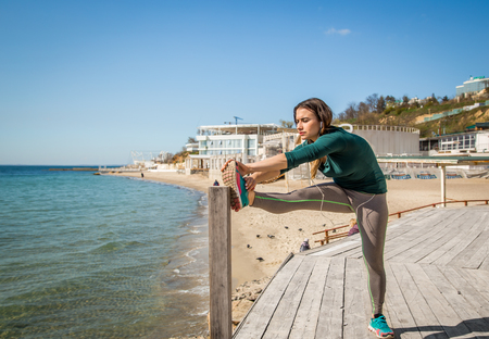 Girl in sportswear doing stretching by the sea fitness ,sports motivation,sport,fitness Stock Photo